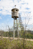 Abandoned sentry box tower  by a net with barbed wire. Royalty Free Stock Photography