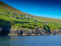 Abandoned settlement on Blasket island. View from a fishing boat near the Slea Head on the Dingle Peninsula in Ireland with a clear deep blue sky Royalty Free Stock Photography