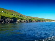 Abandoned settlement on Blasket island. View from a fishing boat near the Slea Head on the Dingle Peninsula in Ireland with a clear deep blue sky Royalty Free Stock Photos