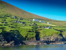 Abandoned settlement on Blasket island. View from a fishing boat near the Slea Head on the Dingle Peninsula in Ireland with a clear deep blue sky Stock Images
