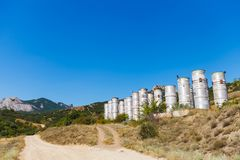Abandoned metal cylindrical treatment facilities on the road royalty free stock images