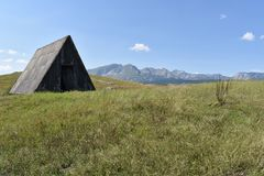 The abandoned shepherds traditional wooden hut and the Durmitor mountain in the distance Stock Photo