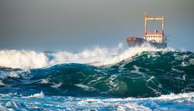 Abandoned Ship In The Stormy Ocean With Big Wind Waves During Sunset Stock Photo