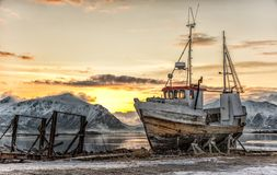 Abandoned ship in Lofoten, Norway. With sun rising behind royalty free stock photography
