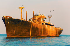 Abandoned ship polluting water Stock Photo