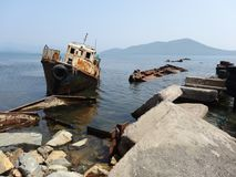 Abandoned ships. On the shore of the Sea of ​​Japan in Primorsky Krai against the background of Putyatin Island. Cemetery of ships Stock Images