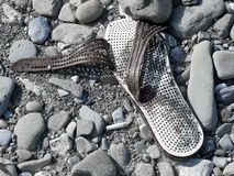 Abandoned shoe on stony shore. Migrant concept. Royalty Free Stock Photography
