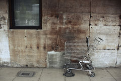 Abandoned Shopping Cart. An empty, metal shopping cart in front of a grungy, concrete wall Royalty Free Stock Photography