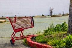 Abandoned Shopping Cart At Failed Business Building. Abandoned Red Shopping Cart In Parking Lot At Failed Business Building Royalty Free Stock Photos