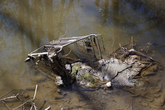 Abandoned shopping trolley in muddy water Stock Photography