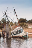 Abandoned shrimp boat half sunk. Abandoned wrecked shrimp boat tied to a pier badly damaged and half sunk Stock Photo