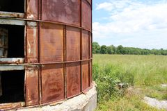 Abandoned silo next to overgrown field Royalty Free Stock Image
