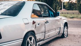 Abandoned silver car on the road, car junk. Broken and crumpled car transport is on the street stock image