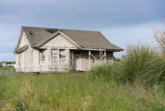 Abandoned single family home with wooden siding as fixer upper property stock image
