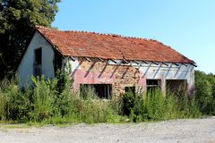 Abandoned small store brick building destroyed in war surrounded with trees and other vegetation. Abandoned small store red brick building destroyed in war with stock photos