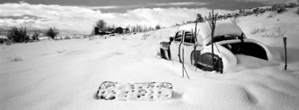Abandoned in the Snow. A panoramic view of several abandoned items including an old car, a box spring and an old house, all covered with a fresh blanket of snow royalty free stock photos