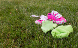 Abandoned socks and shoes. Girl's green socks and pink shoes abandoned on the grass Royalty Free Stock Photography