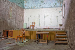 Abandoned stage. Old messy room with a stage, paint peeling off the walls Royalty Free Stock Images