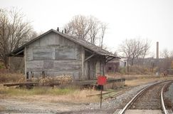 Abandoned Station. An abandoned train station building sits close to the track.  Building is in srious dis-repair Stock Photo