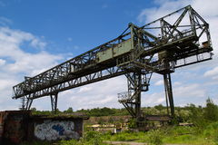 Abandoned Steel Facility. Large abandoned crane for loading and unloading bulk resources, as well as vandalized buildings, located at the former steel production Royalty Free Stock Photography