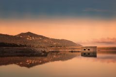 Abandoned stone building reflected in lake at sunset Royalty Free Stock Image