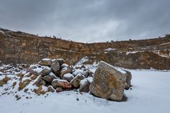 Abandoned stone quarry with big rock covered with snow near Brno, Czech republic royalty free stock photos