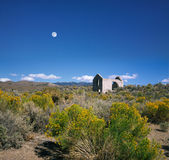 Abandoned Stone Shack. A Daylight Moon Overlooking An Abandoned And Roofless Stone Shack In The Nevada Desert Near Death Valley, USA Royalty Free Stock Photo