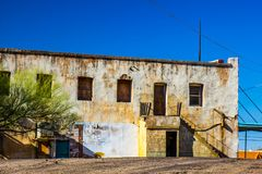 Abandoned Stucco Building With Boarded Up Windows & Doors. Abandoned Two Story Building In Disrepair & With Boarded Up Windows & Doors royalty free stock image