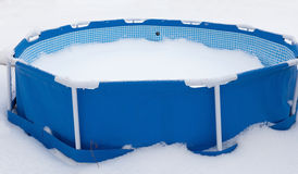 Abandoned swimming pool at winter, surrounded with snow Stock Photo