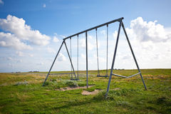 Abandoned swing on a field Royalty Free Stock Photo