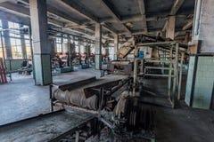Abandoned tea factory with remnant of rusty equipment. Broken conveyor belt stock photography