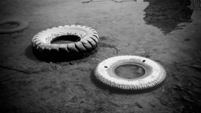 Abandoned tire on the water sea or lake pond with black and white style color royalty free stock image