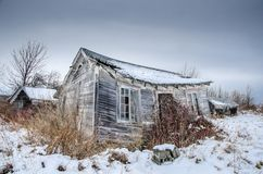 Abandoned tourist cabin in field with snow stock image