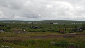 Abandoned town in tundra in nothern Russia. Abandoned town in tundra in nothern part of russia with cloudy sky in summer royalty free stock images