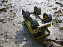 Abandoned Toy Truck on Playground. An abandoned toy truck lays upside down on a silt covered playground after a flood royalty free stock photo