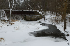 Abandoned Train Bridge Over Stream in Snow Stock Image