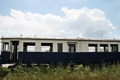 An abandoned train in a field. In a sunny day with some white clouds Stock Photography