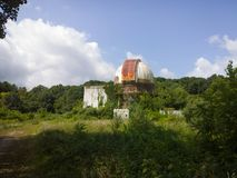 Abandoned. Trees and vegetation overrunning a rusting, abandoned observatory under the clouds and blue sky stock images