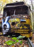 Abandoned trolley car on rails with small tree. Abandoned trolley car painted with graffiti on rails in woods during fall foliage and small tree Royalty Free Stock Photo