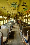 Abandoned Trolley Cars with Inside Seats with Graffiti. Abandoned trolley cars with ripped seats and ceiling painted with graffiti stock images