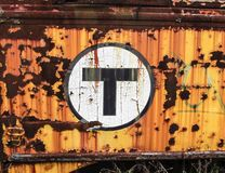 Abandoned trolley cars transit symbol close up. Abandoned trolley cars painted with graffiti in woods   transit symbol close up Stock Photos