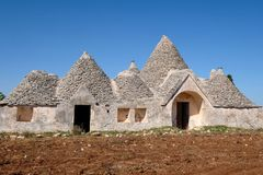 Abandoned Trulli house with multiple conical roofs located in a field in the area of Cisternino / Alberobello in Puglia, Italy