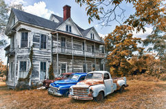 Abandoned Two Story Farmhouse with Three Vintage Automobiles Stock Photo
