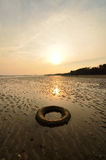 Abandoned tyre on the beach when the sun goes down Royalty Free Stock Photography