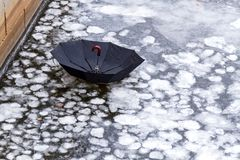 Umbrella on an ice of city river or lake royalty free stock photo