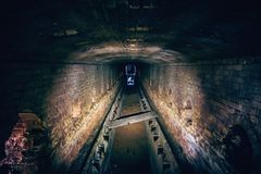 Abandoned underground sewer brick tunnel, dark dirty industrial corridor, tube perspective view Royalty Free Stock Photo