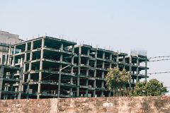 Abandoned unfinished building. Behind the fence. long-term Royalty Free Stock Photo