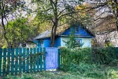Abandoned village in Chernobyl exclusion zone with buildings taken over by vegetation Stock Photography