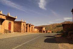 Abandoned village of clay houses along empty road in Atlas mountains, Morocco stock photography