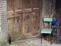 Abandoned village doorway with chair and wine bottle. Poignant. Stock Photography